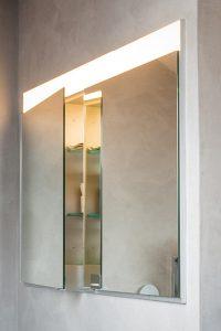 Der Spiegelschrank ist in die Wand eingebaut.