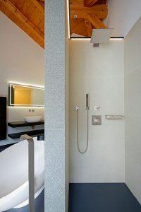 Die Trennwand teilt ein großes Badezimmer in klare Funktionsbereiche.