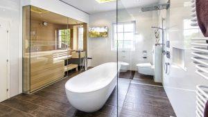 So geht Wellness zuhause: Eine freistehende Badewanne für zwei, eine große, bodenebene Dusche und eine moderne Saunakabine bieten in diesem Badezimmer Möglichkeiten zur Entspannung